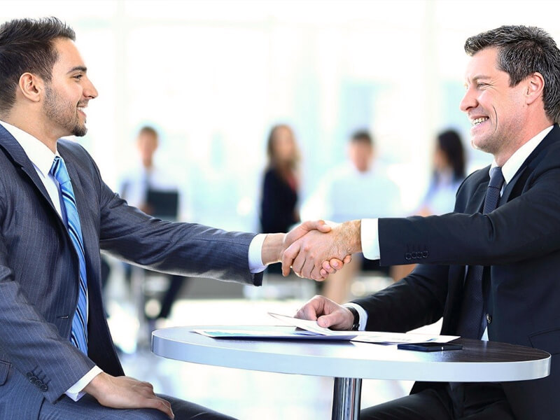 Two men in suits shake hands after successul networking