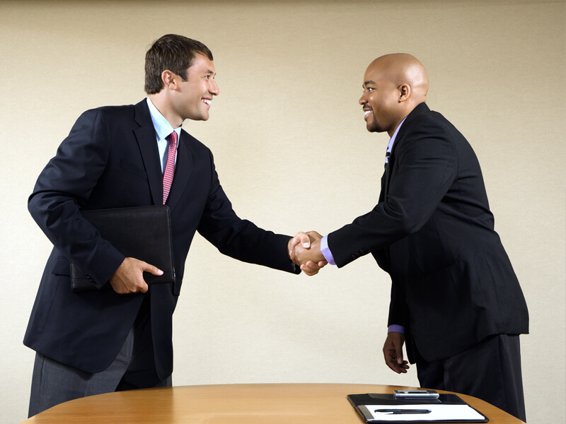 job seeker and hiring manager shaking hands after job interview